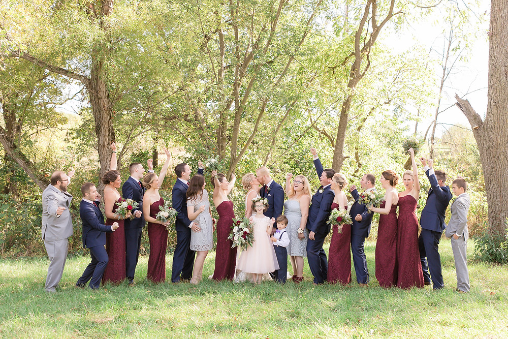 Flower bouquets by studio bloom iowa wedding florist held by cheering bridal party in burgundy dresses and navy suits