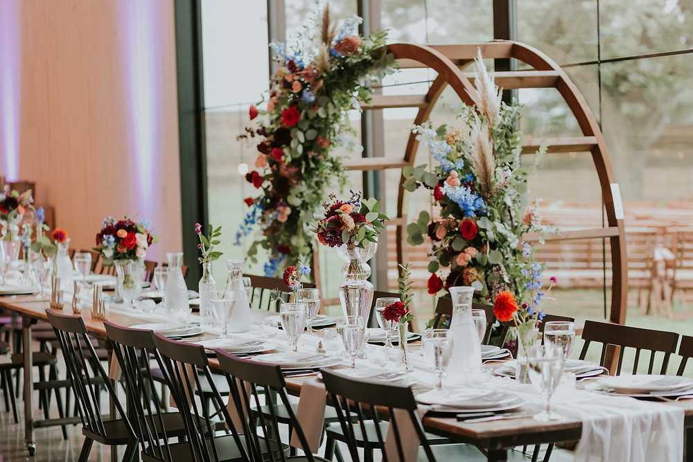 Colorful floral moongate arch behind head table by Studio Bloom Iowa wedding florist at Little Lights on the Lane
