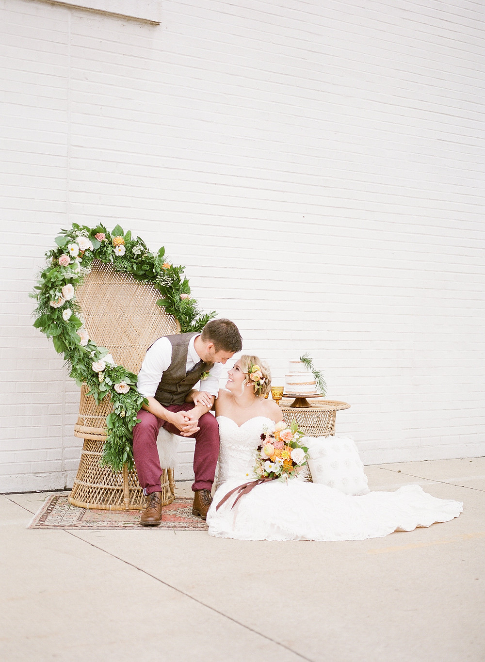 Bride and groom sitting in wicker peacock chair decorated with garland of flowers and greenery by studio bloom iowa weddings