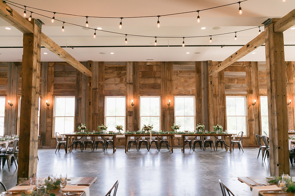 wedding head table at rapid creek cidery with rustic walls and farm tables with bridal party bouquets by studio bloom iowa