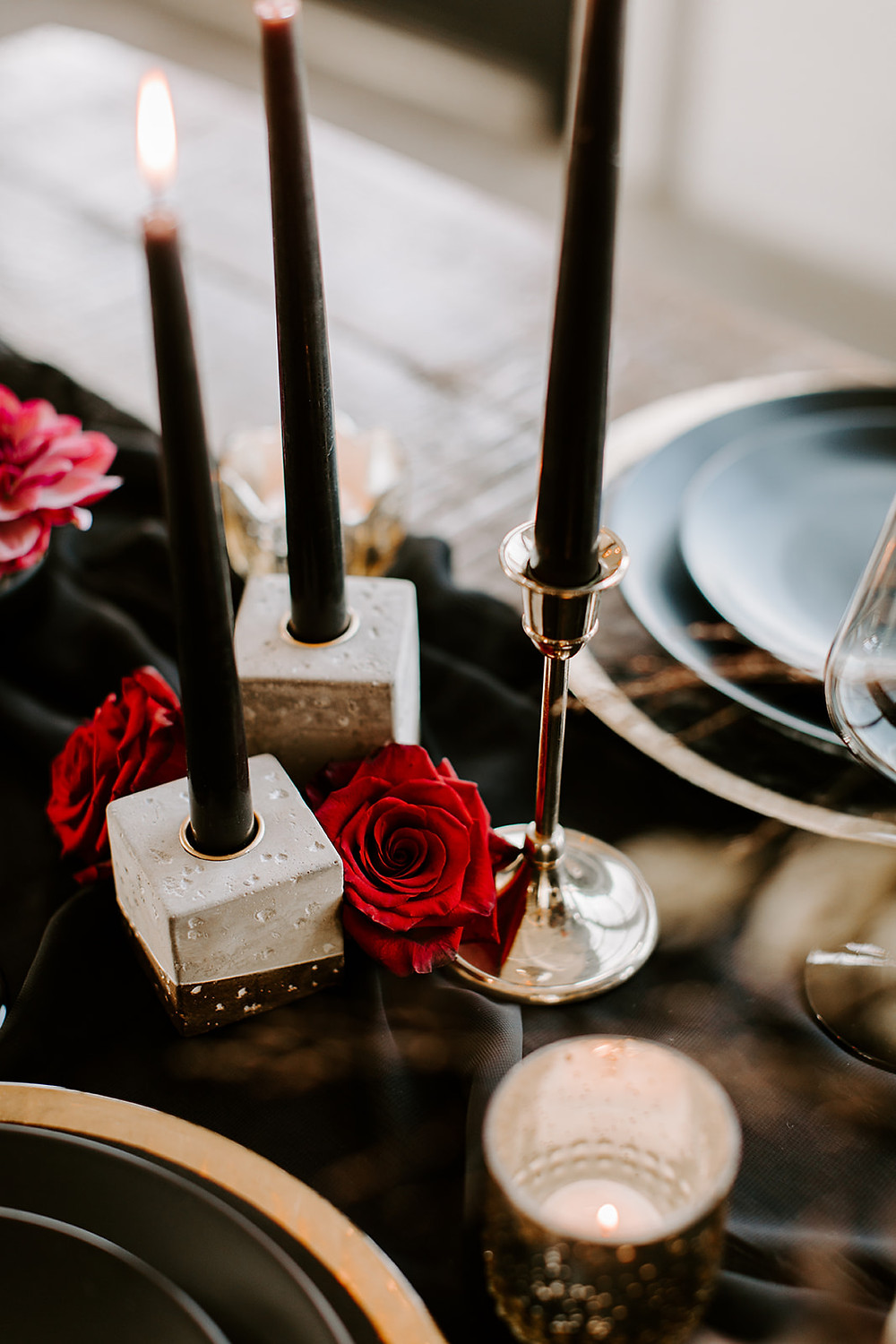 black taper candles accented with red roses for a wedding reception
