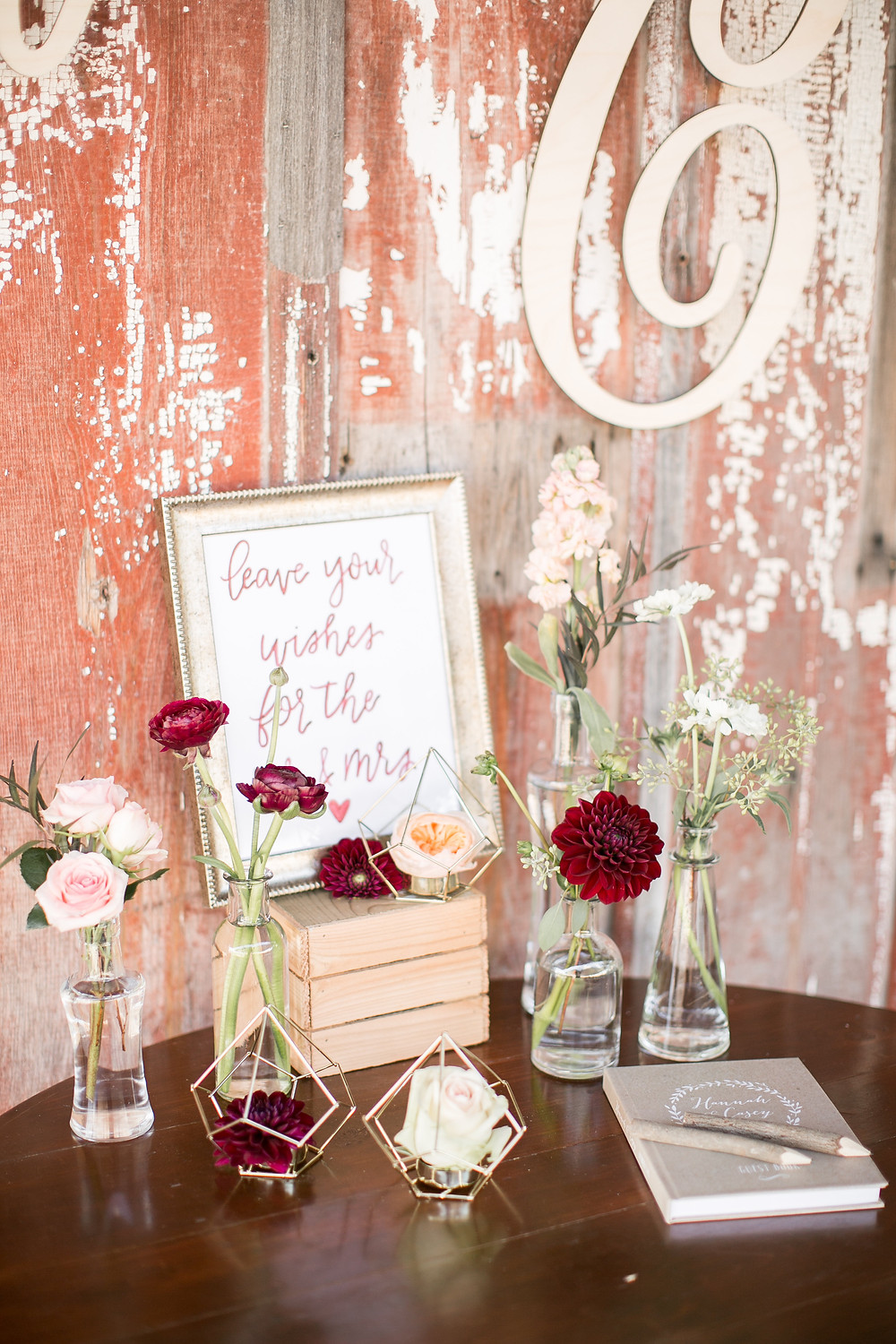 wedding guest sign in table with budvases of flowers at sutliff cider barn wedding in iowa