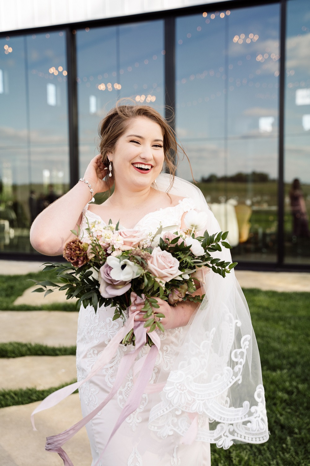 bride holding Studio Bloom Iowa bridal bouquet in mauve and blush at Little Lights