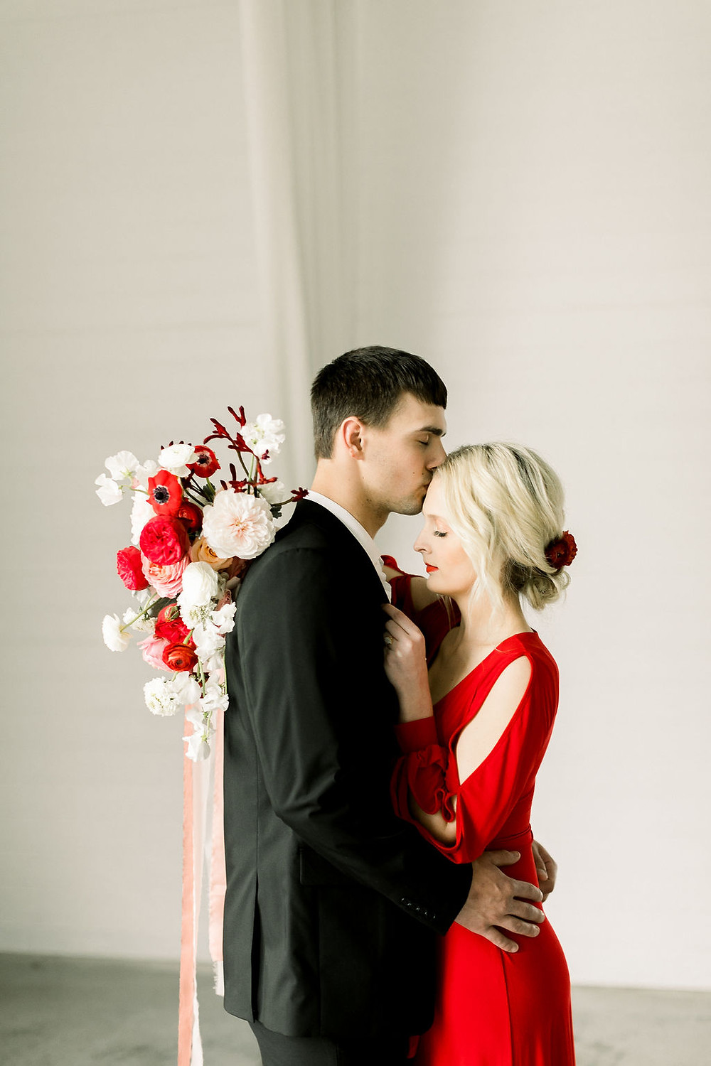 Groom kissing bride in red dress holding modern blush and red bridal bouquet by Studio Bloom Iowa at Ashton Hill