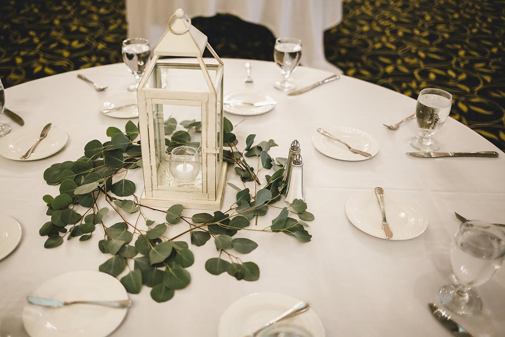 wedding reception centerpiece of white lantern with eucalyptus on white tablecloth