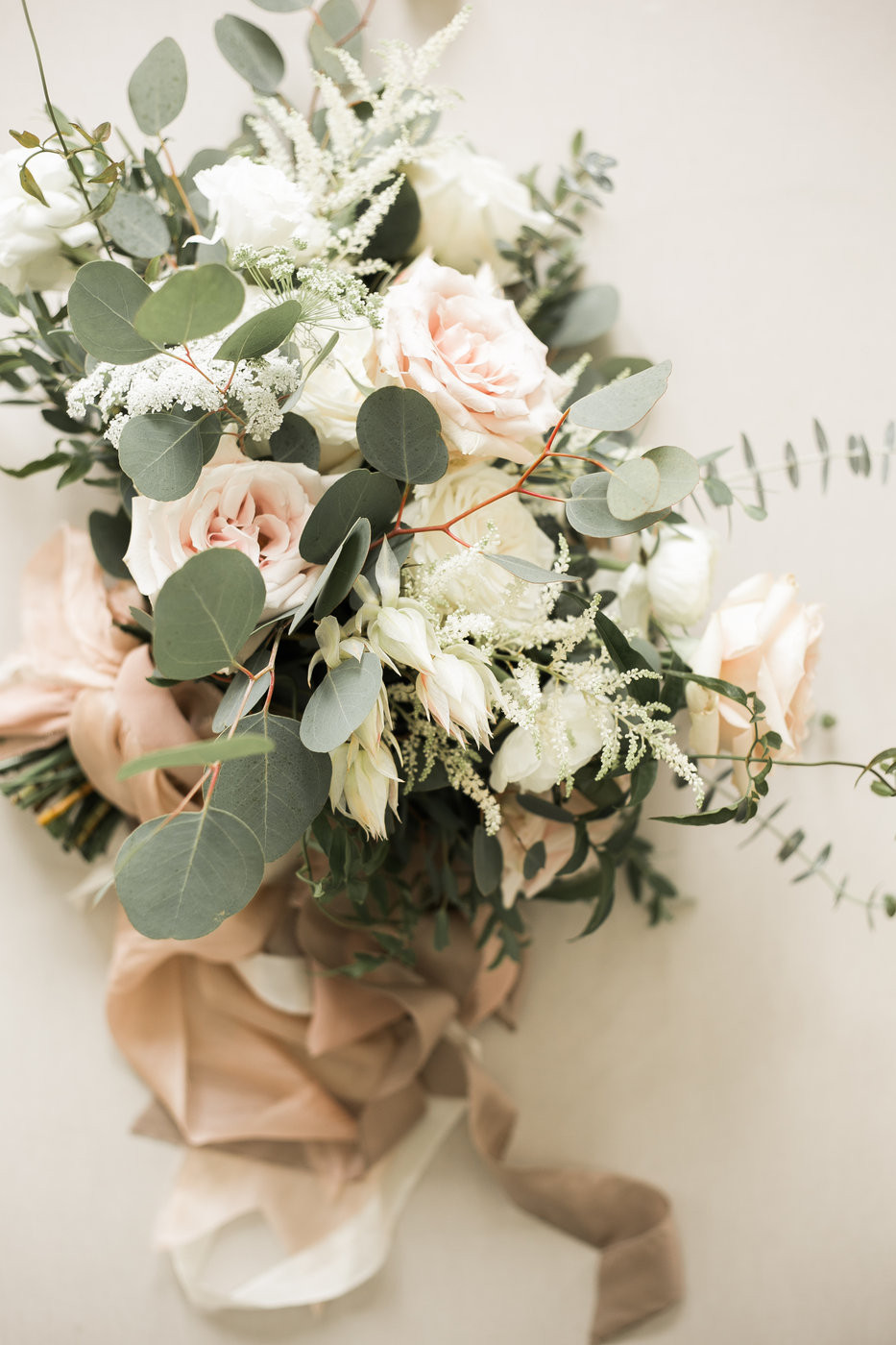 bridal bouquet by studio bloom iowa of roses, blushing bride protea, ranunculus, astilbe, and eucalyptus