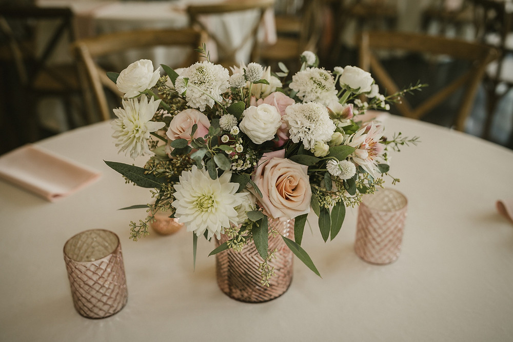 blush and white wedding centerpiece by studio bloom iowa with dahlias, roses, protea, scabiosa and eucalyptus in pink vase