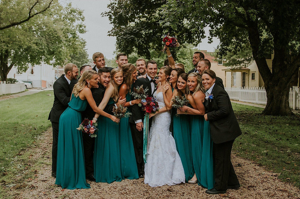 bridal party cheering with jeweltone dresses and bouquets by Studio Bloom Iowa