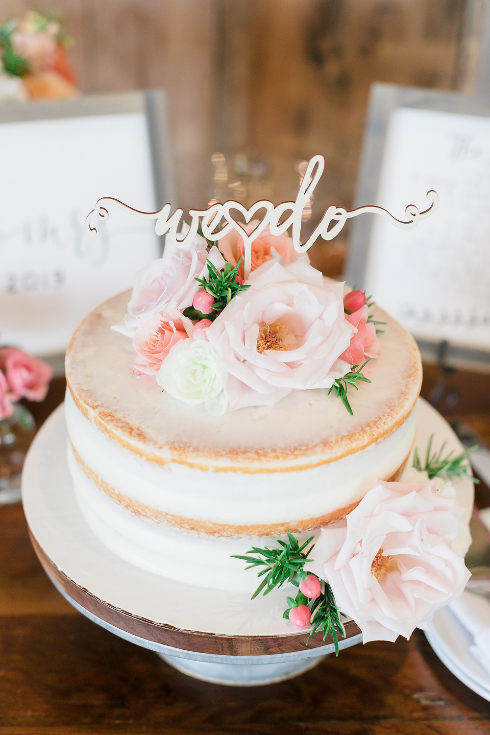We do wood cake topper on naked wedding cake with pink and peach roses by Studio Bloom Iowa