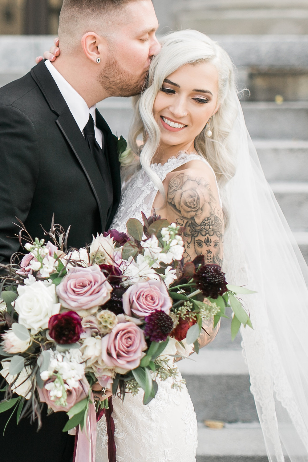 groom kissing tattooed bride holding bridal bouquet of mauve roses, burgundy ranunculus, and scabiosa by studio bloom iowa