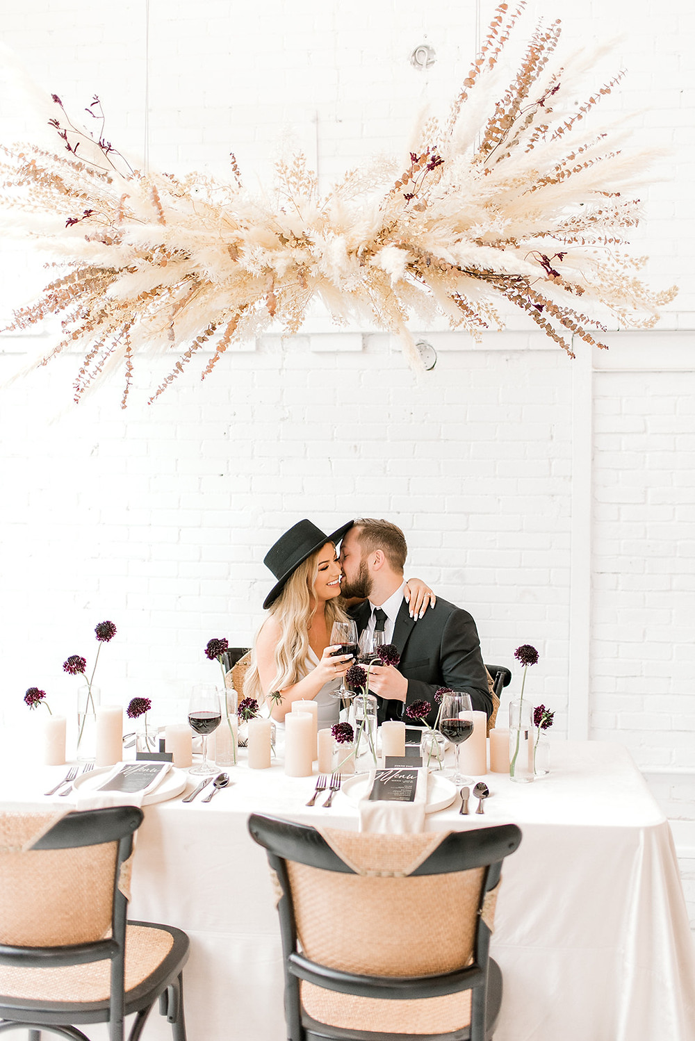 hipster bride and groom under suspended pampas grass centerpiece by Studio Bloom Iowa wedding florist