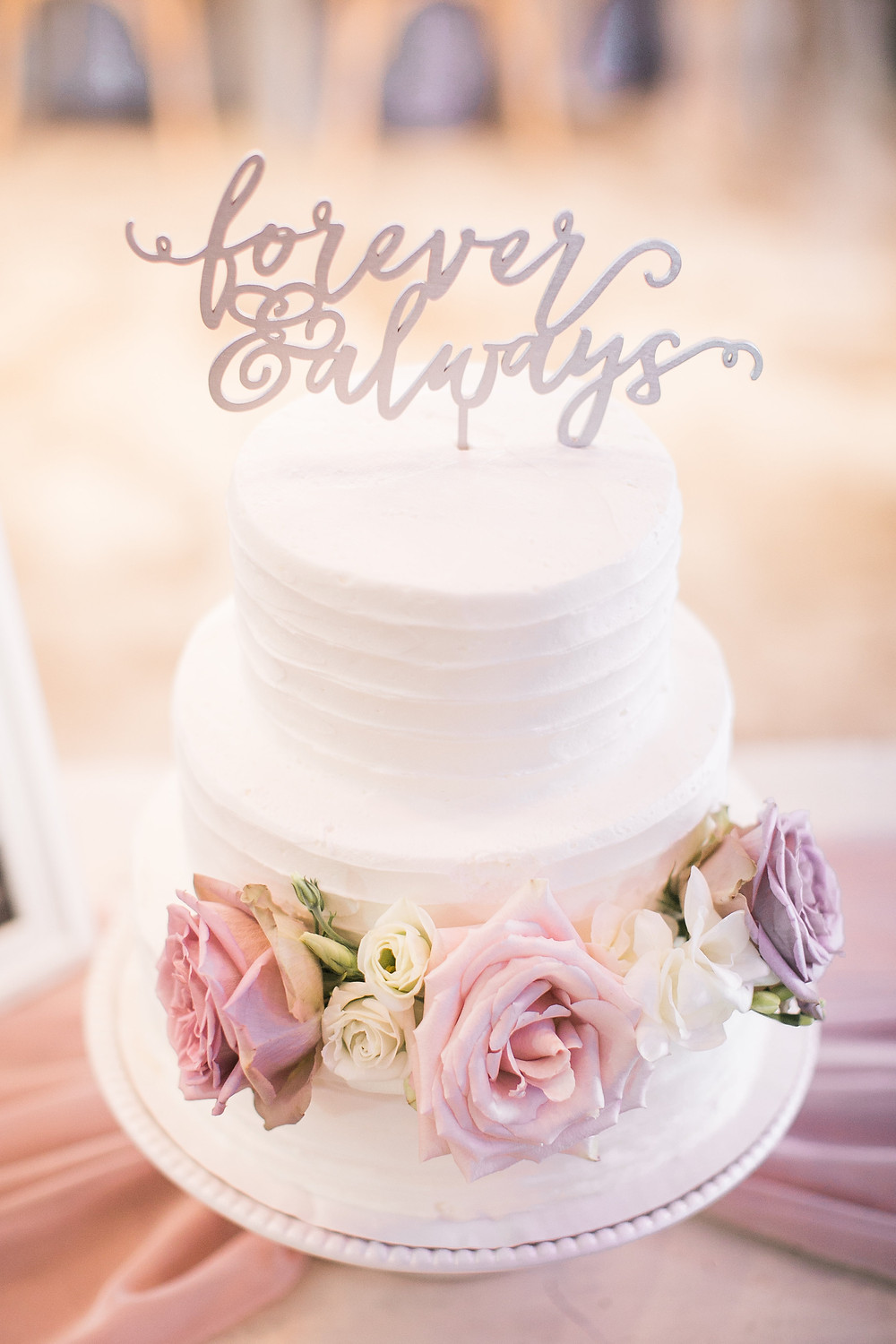 white wedding cake with mauve and blush roses and a silver painted wood forever & always cake topper by studio bloom iowa