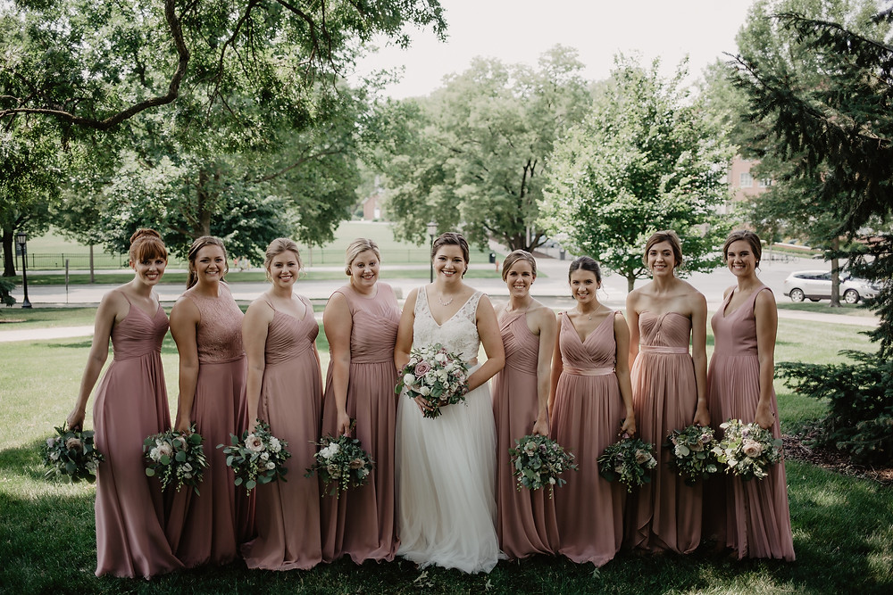 bride and bridesmaids in mauve dresses with mauve and white bouquets with eucalyptus by studio bloom iowa