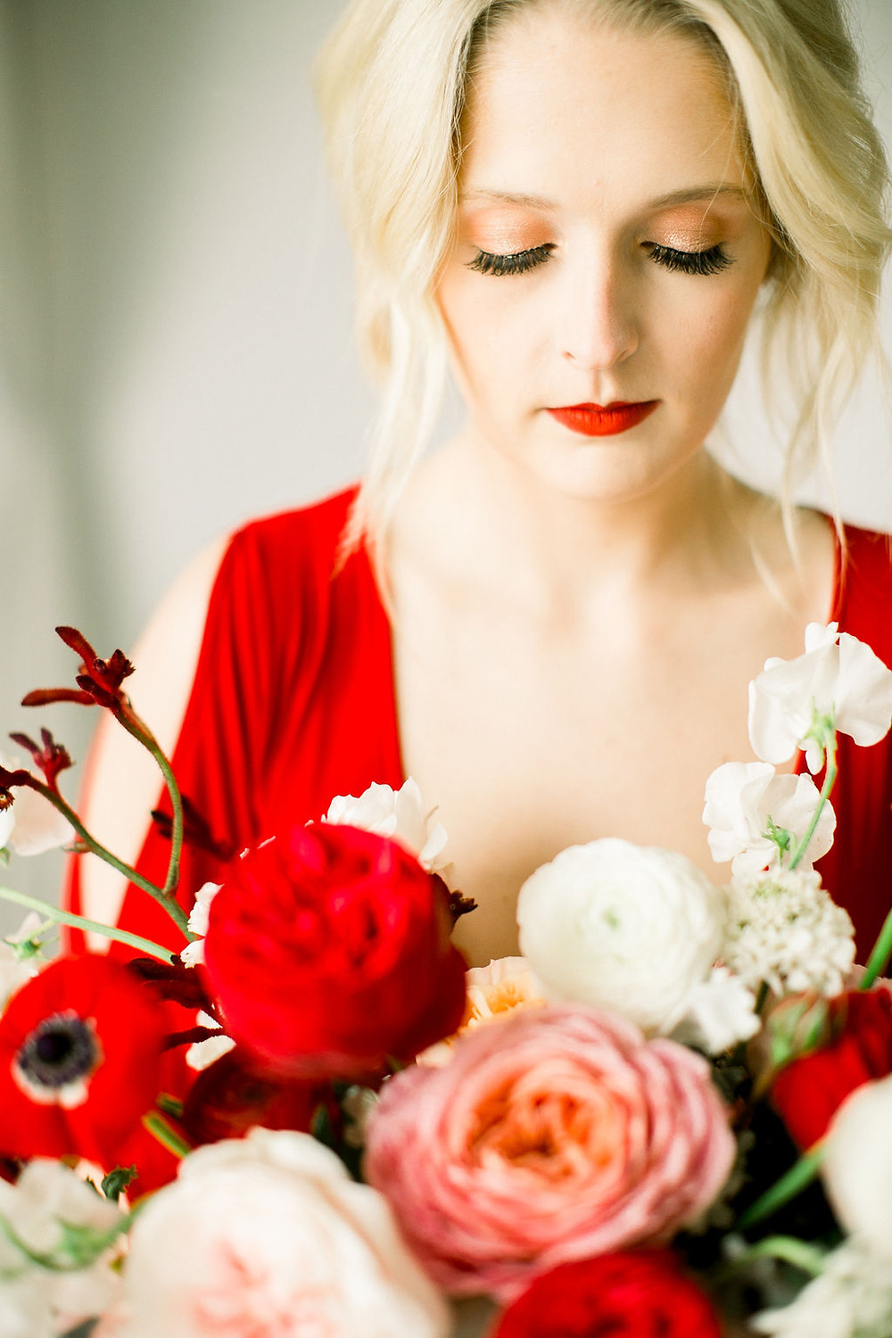 Bride in vibrant red dress holding bouquet by Studio Bloom Iowa