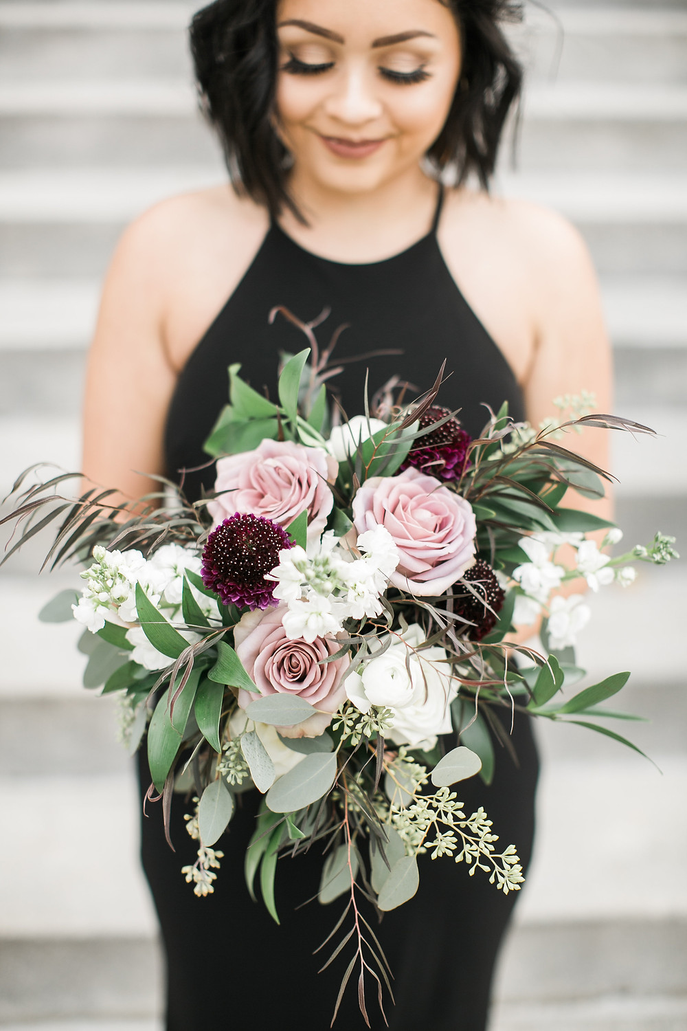 bridesmaid bouquet by studio bloom iowa of mauve roses, burgundy ranunculus, white stock, and greenery wearing black dress
