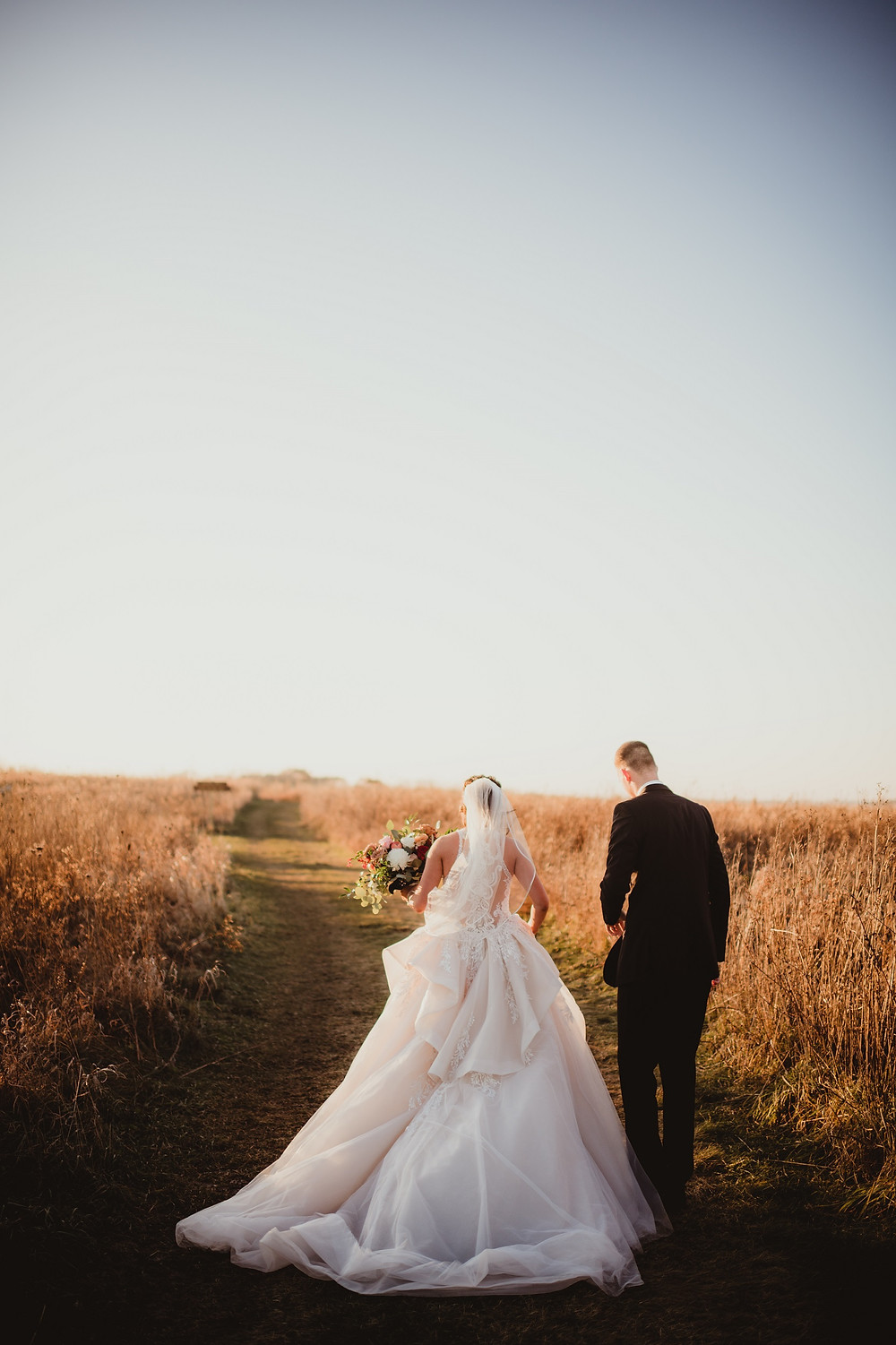 bride in elegant bridal gown and groom walking in field at sunset in iowa