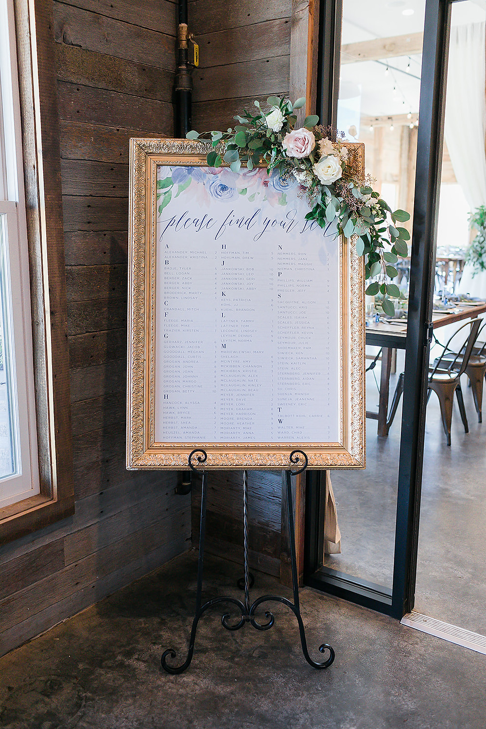 Seating chart in gold frame with flowers by Studio Bloom Iowa at Rapid Creek Cidery