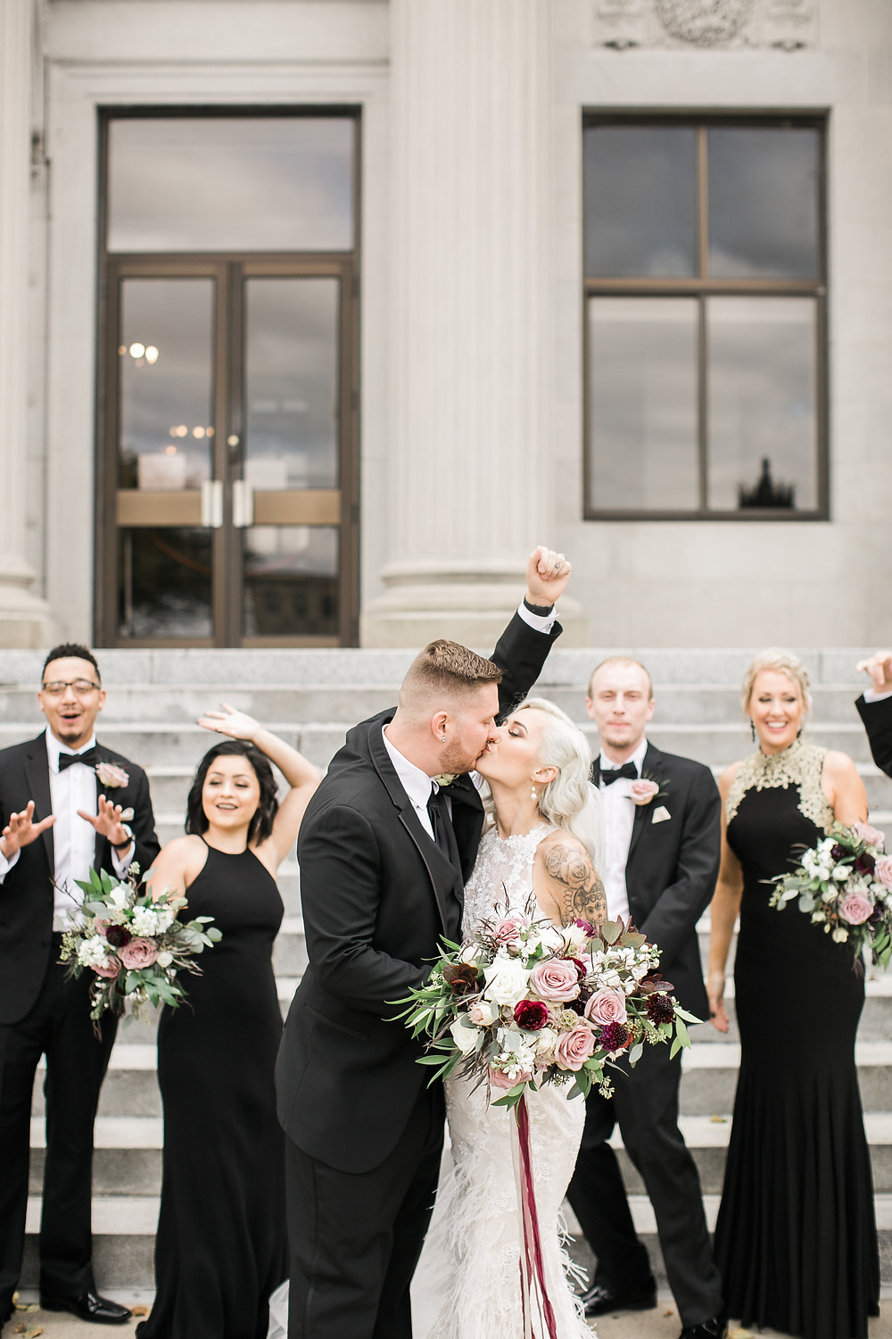 bride and groom kissing holding wedding bouquets by studio bloom iowa with bridal party cheering in black dresses and suits