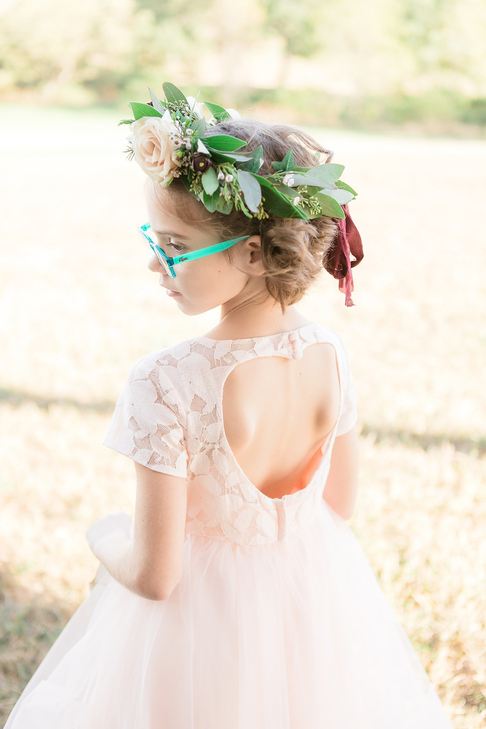 flower girl with flower crown wearing blush dress and aqua lacoste glasses