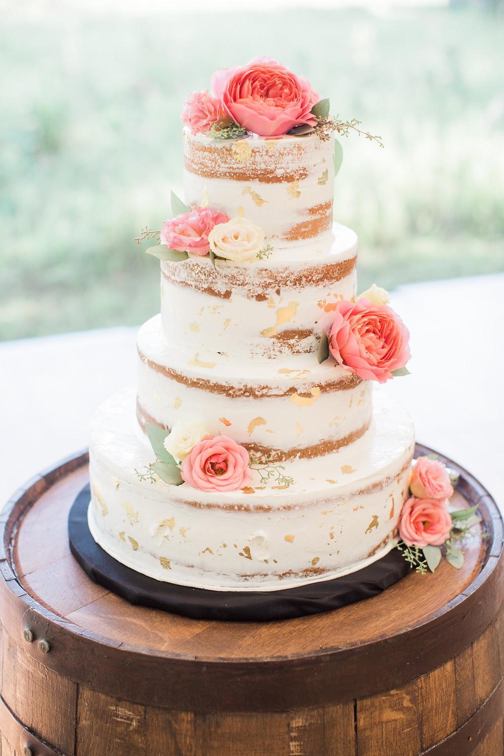 Elegant 4 tier naked wedding cake with gold leaf on a barrel and coral garden roses floral accents by studio bloom iowa