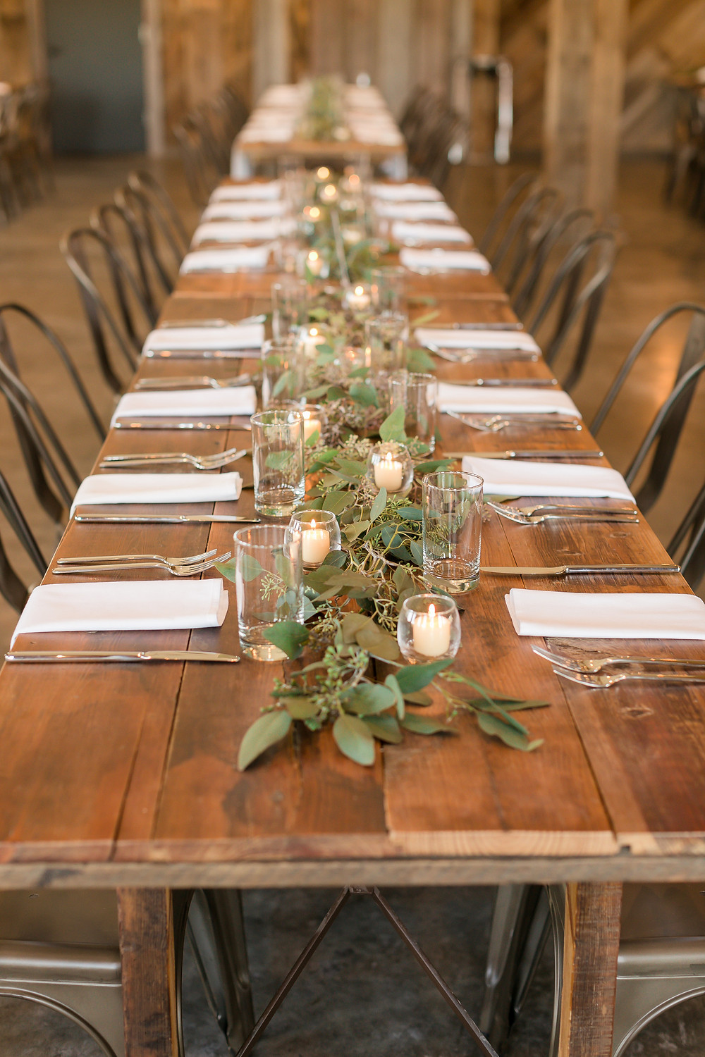 eucalyptus greenery and candles on rustic farm tables at rapid creek cidery by studio bloom iowa florist iowa city