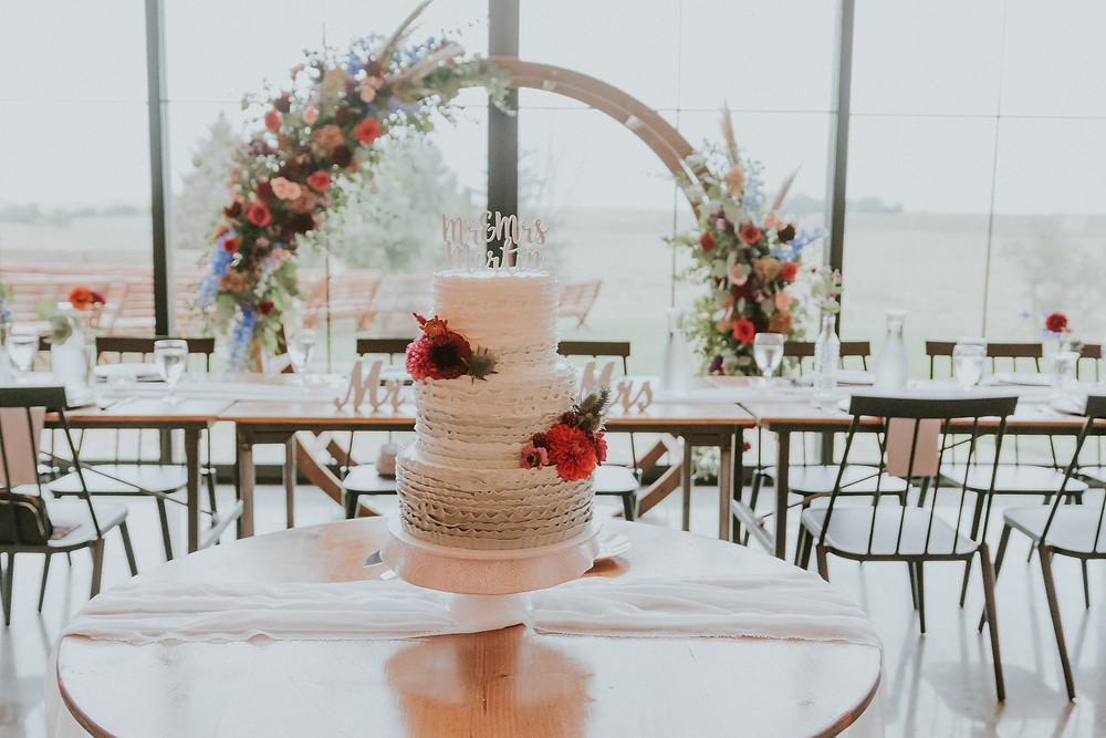 cake in front of moongate arch with flowers by Studio Bloom Iowa