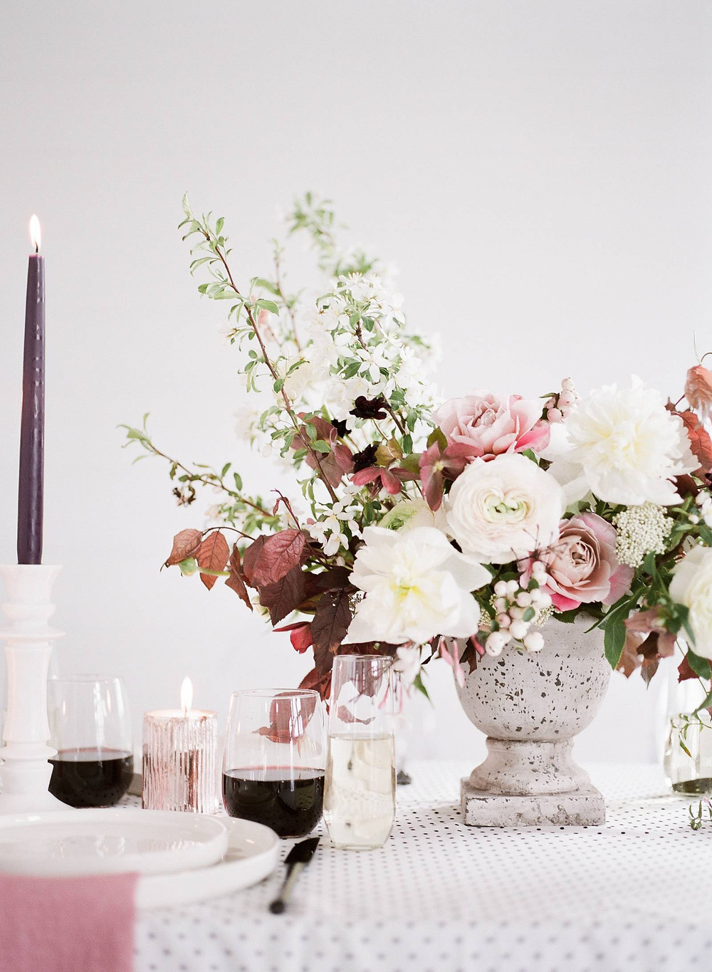 Modern garden centerpiece by Studio Bloom Iowa of roses, ranunculus, peonies, plum, and flowering branches in mauve and white