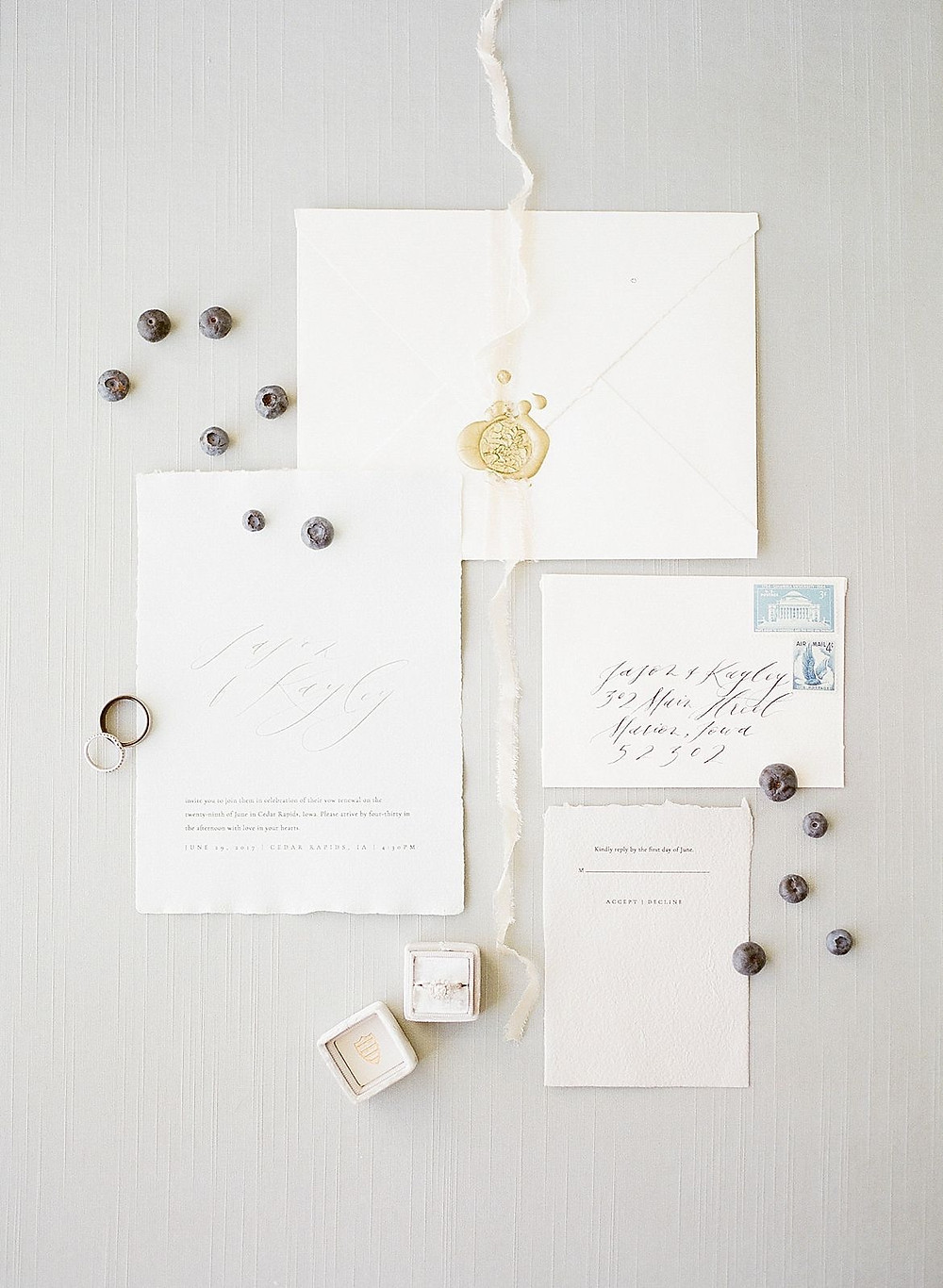 vow renewal calligraphy invitation flatlay with blueberries and wedding rings
