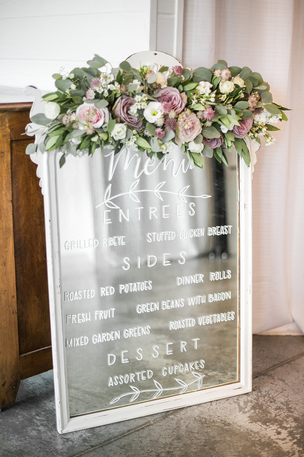 wedding menu written on an antique mirror decorated with flowers by studio bloom iowa in mauve and white at ashton hill