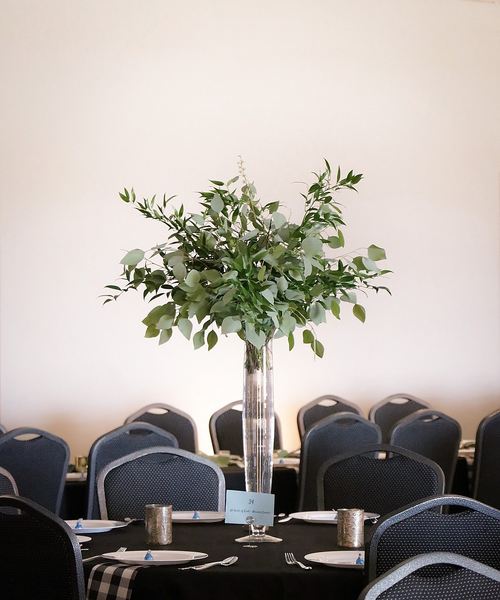 tall greenery centerpiece of eucalyptus and ruscus in clear vase by Studio Bloom Iowa wedding florist