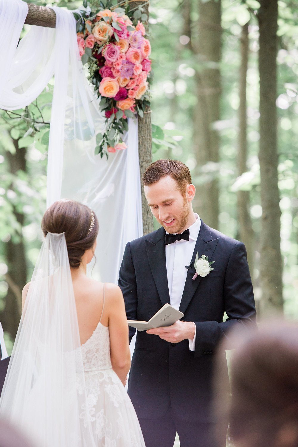 bride and groom exchanging vows in the woods under arbor with pink and peach flower arrangement by studio bloom iowa