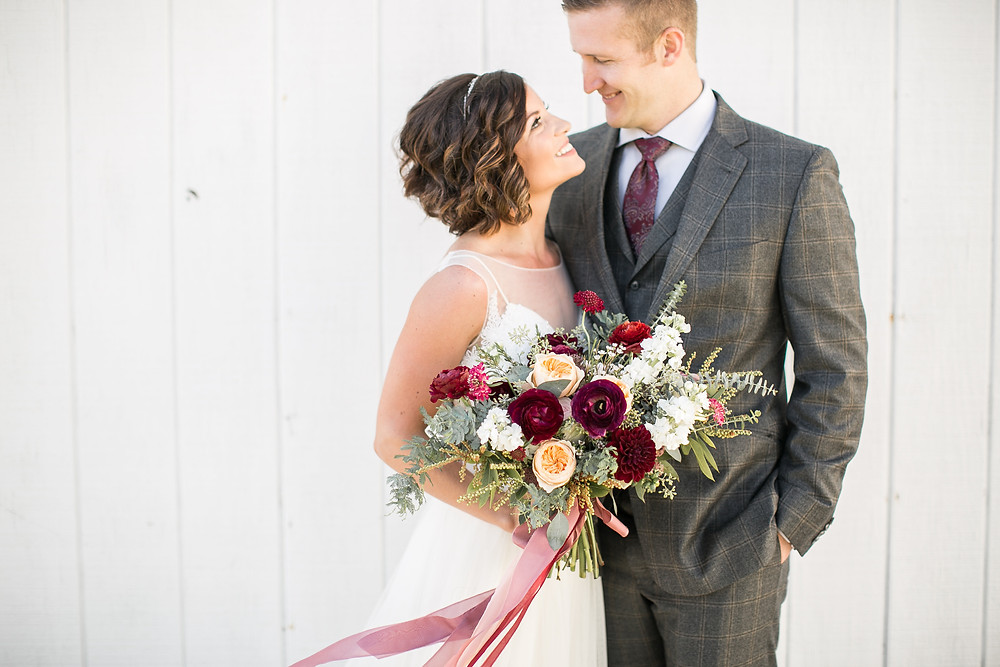 studio bloom iowa lush bridal bouquet with burgundy and blush flowers held by bride and groom posing at Sutliff Cider