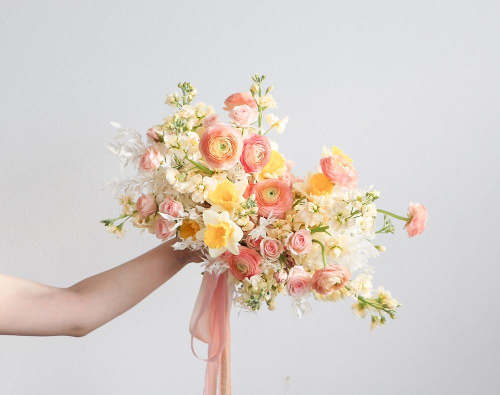 Studio Bloom Iowa spring bridal bouquet in peach, yellow, and cream