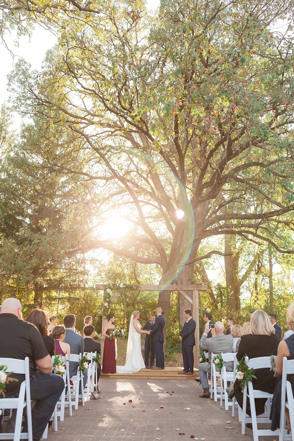 Bride and groom at outdoor wedding ceremony at rapid creek cidery in iowa city
