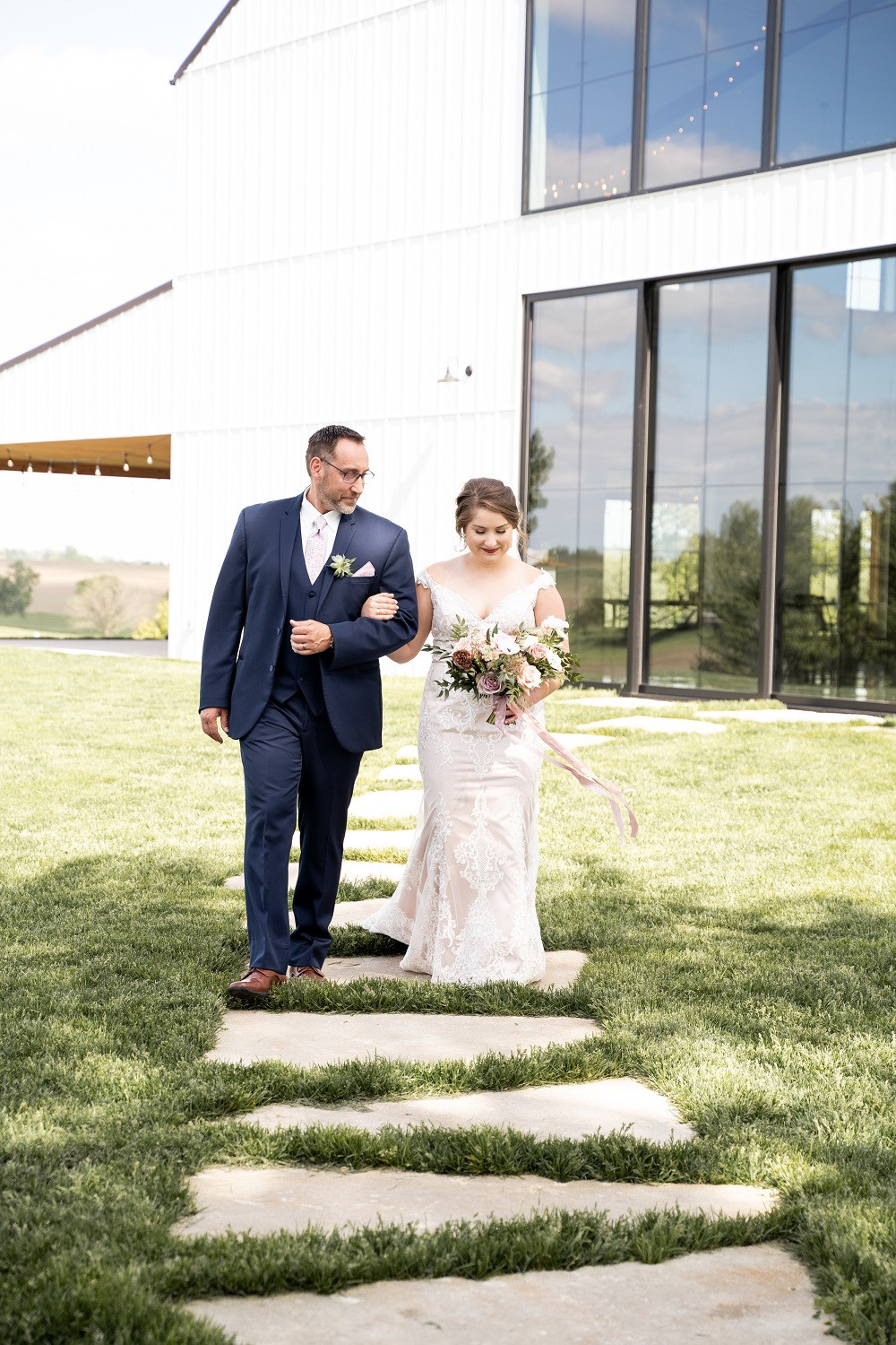 bride walking down the aisle with dad holding bridal bouquet by Studio Bloom Iowa