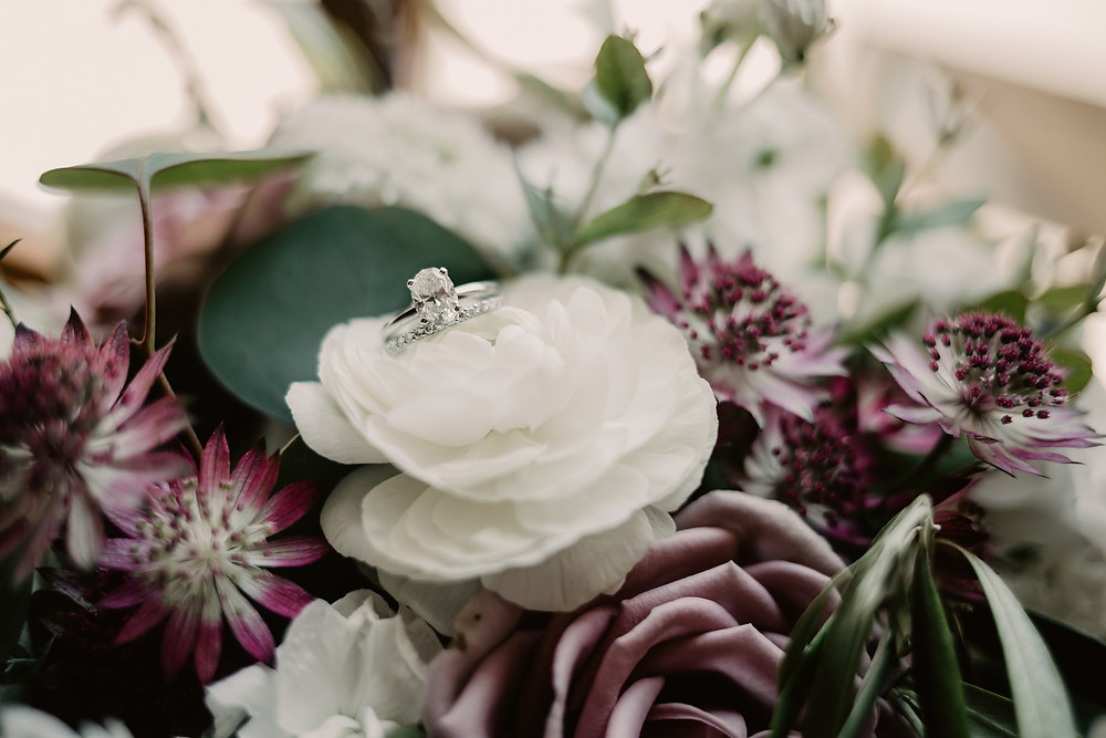 close up detail of wedding rings in white and purple flowers