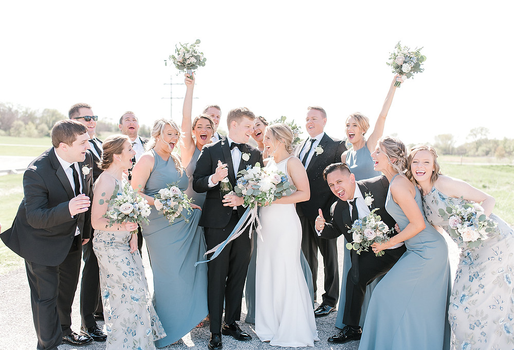 Bridal party in black and slate blue popping champagne and cheering with flower bouquets by Studio Bloom Iowa
