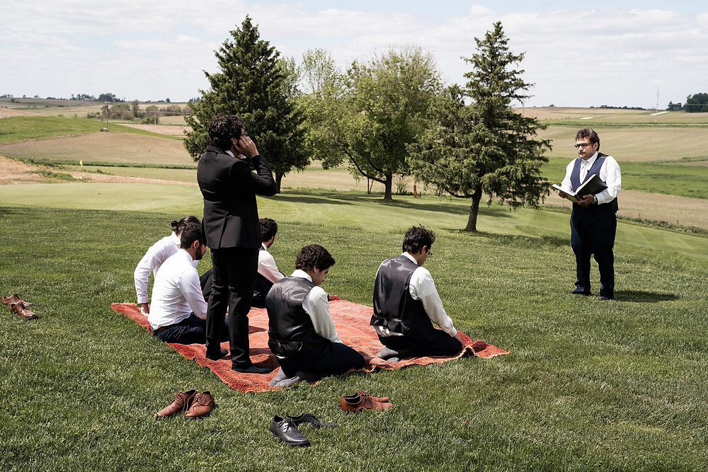 groomsmen praying outside before wedding ceremony