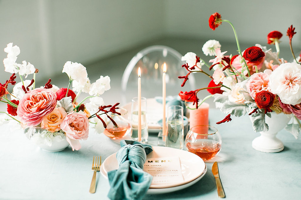 Red and blush wedding reception table centerpiece by Studio Bloom Iowa wedding florist with teal and gold accents and candles