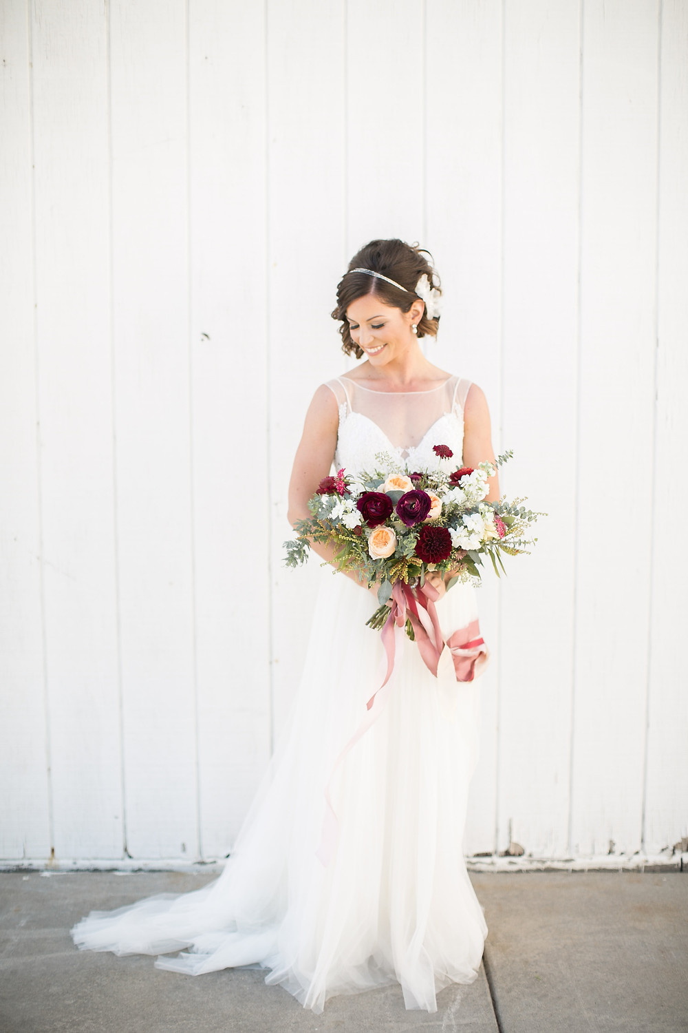 bride holding wedding bouquet by studio bloom iowa of juliet roses, ranunculus, dahlias, and eucalyptus on white barn wall