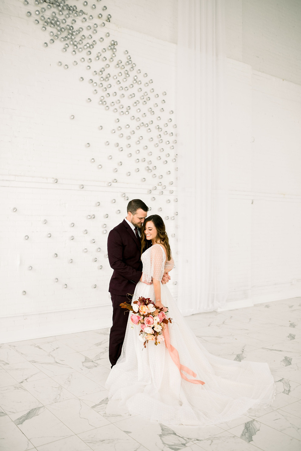 Bride and groom posing at the driftless venue against white brick wall with Studio Bloom Iowa bridal bouquet