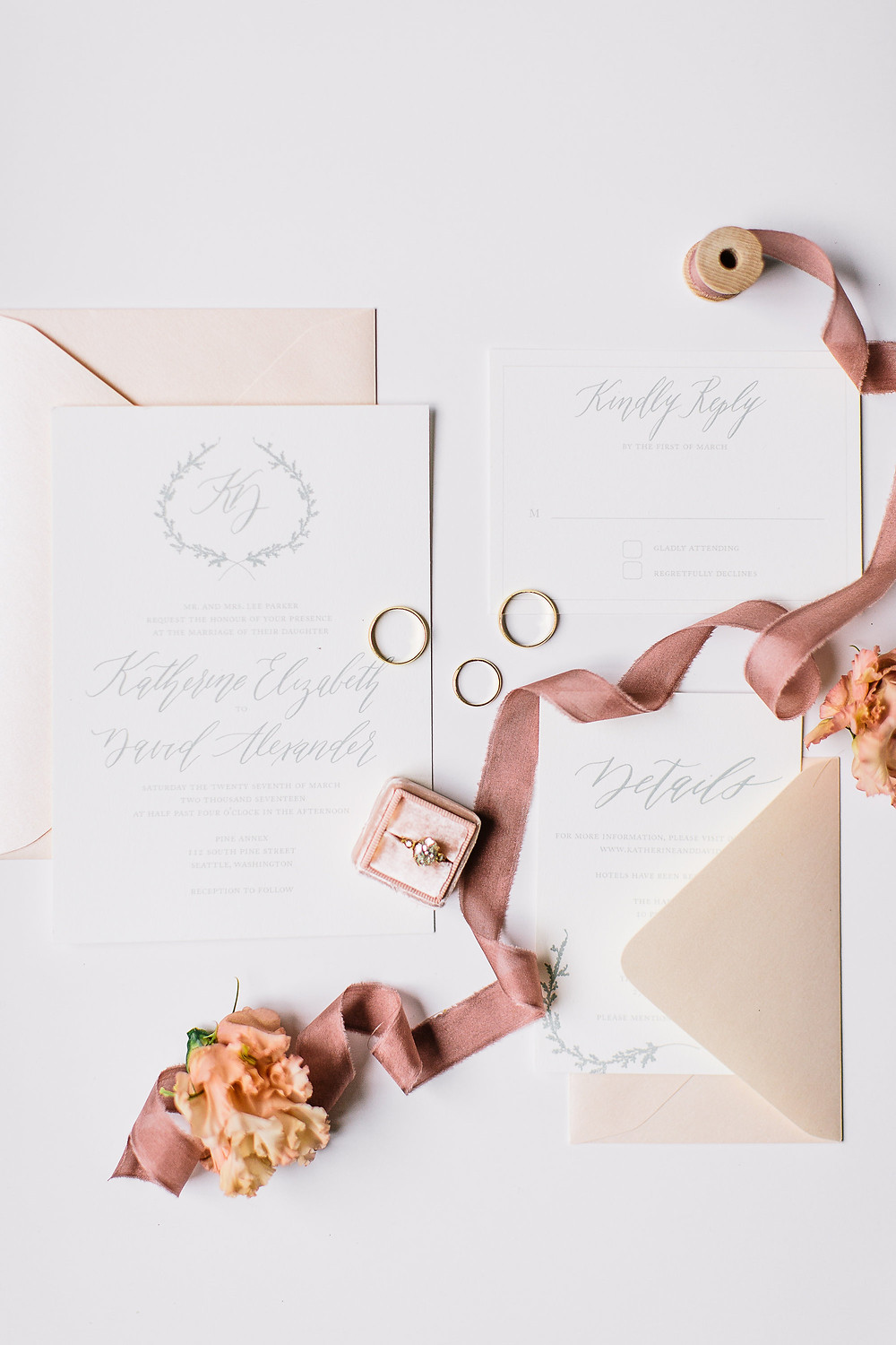 flat lay with calligraphy wedding invitation suite decorated with dusty pink silk ribbon wedding rings and flowers