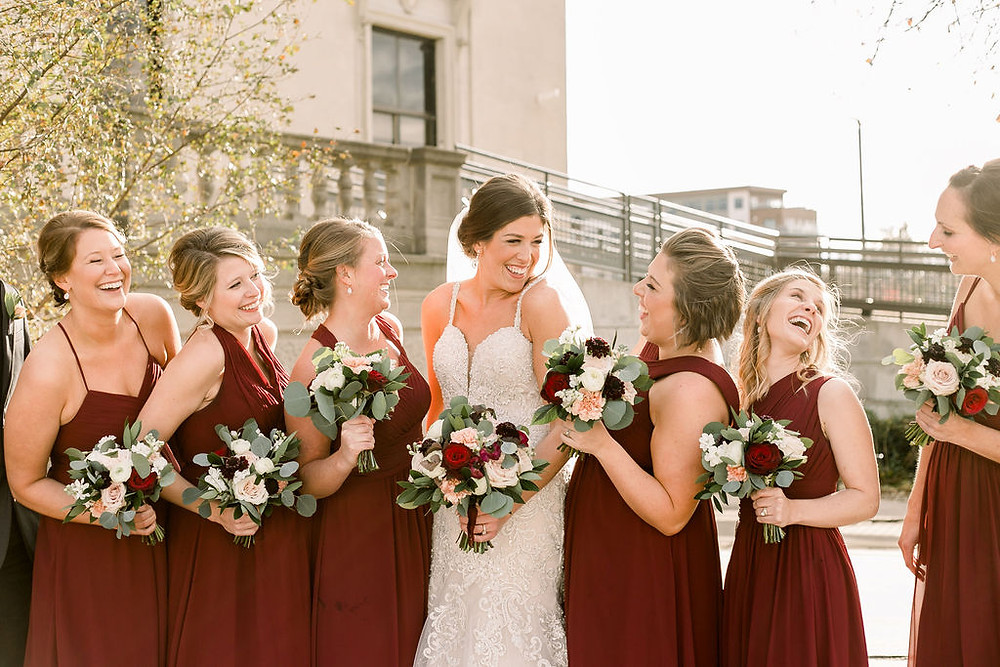 bride and bridesmaids smiling in burgundy dresses holding wedding bouquets by Studio Bloom Iowa burgundy and blush
