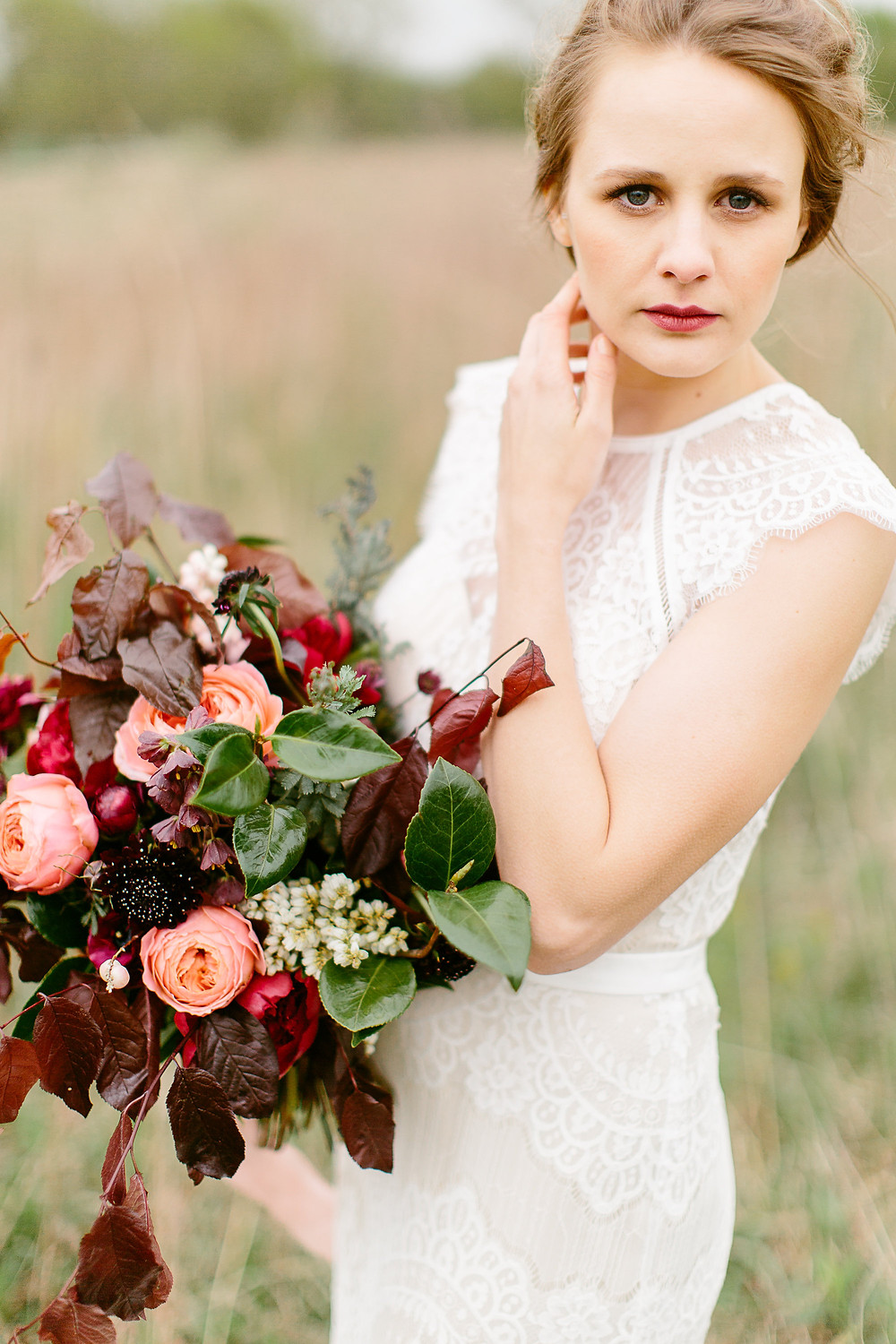 bride posing with lush garden bridal bouquet by studio bloom iowa with peach garden roses and burgundy peonies