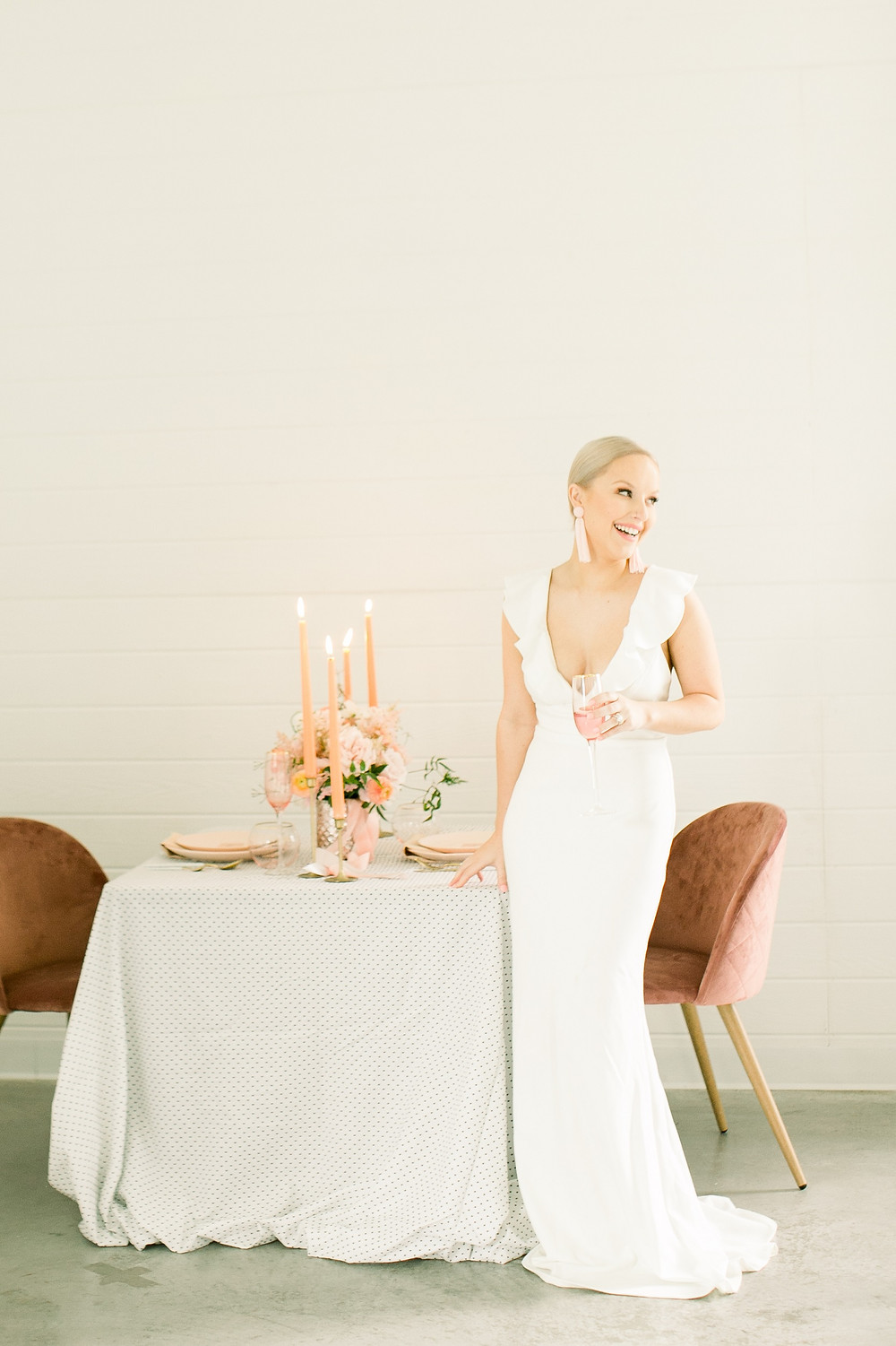 Smiling bride in ruffled dress at table with polka dot linens and velvet chairs and blush centerpiece by Studio Bloom Iowa
