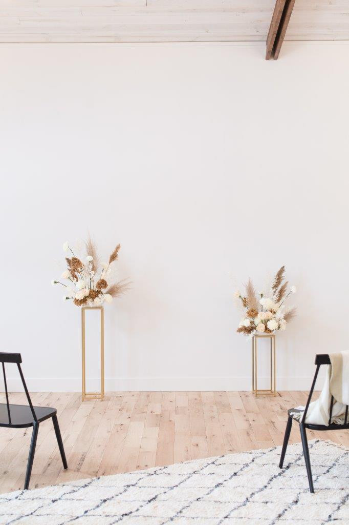 Minimalist wedding ceremony flowers by Studio Bloom Iowa in white and tan on gold stands with roses, pampas, and carnations