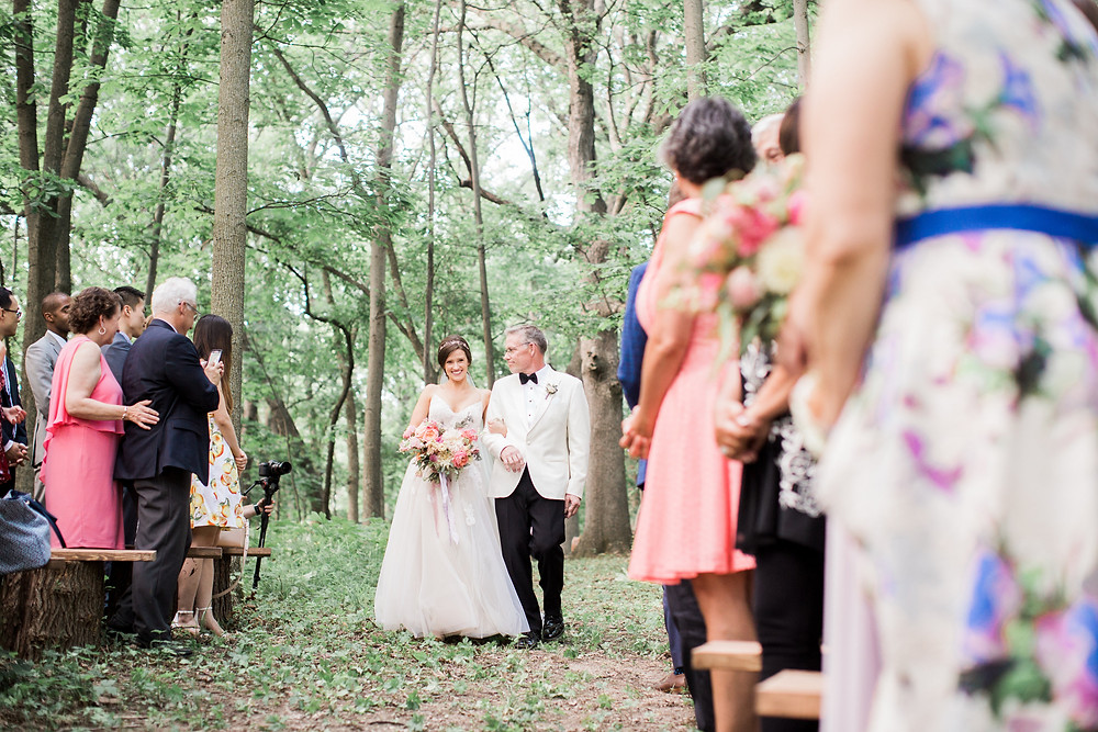 forest wedding ceremony bride and dad walking down the aisle with studio bloom iowa bridal bouquet