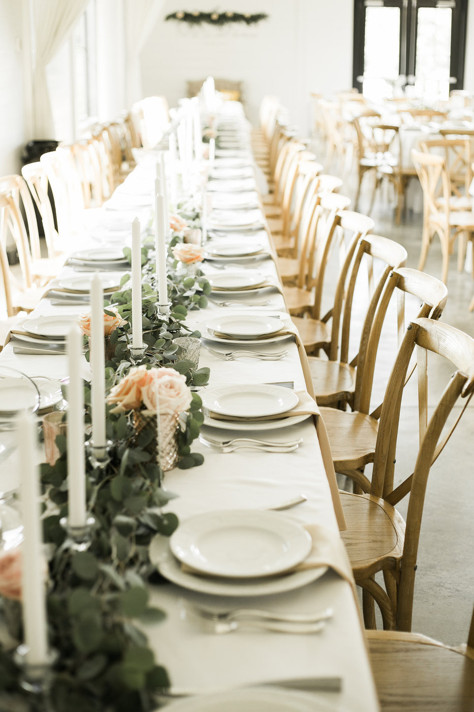 Candles and greenery garland with roses by studio bloom iowa on long banquet tables for wedding guests at ashton hill