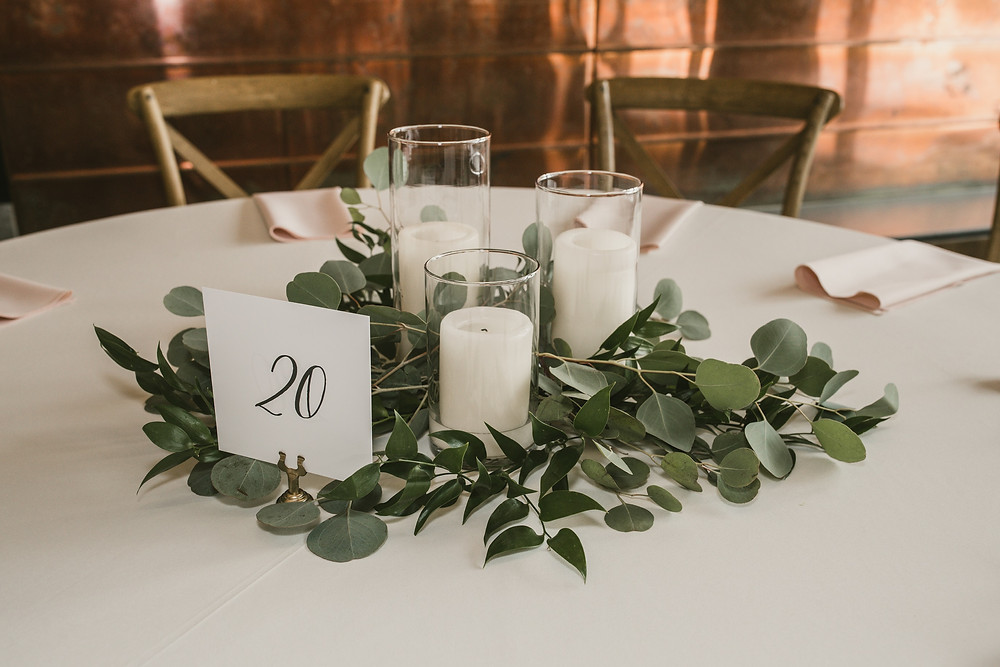 Classic greenery centerpiece with pillar candles, eucalyptus, and ruscus by studio bloom iowa wedding florist