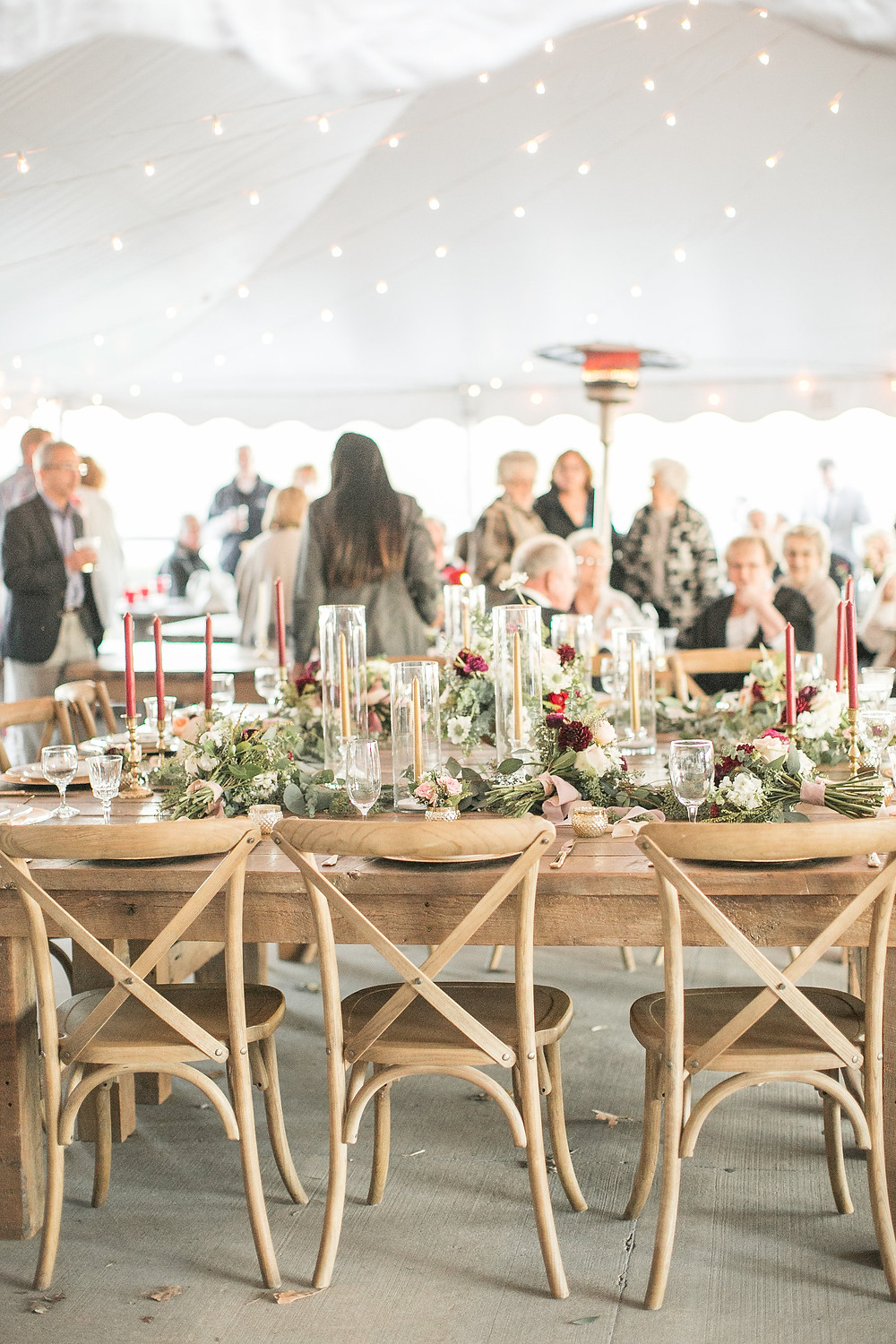 tent wedding reception at sutliff cider barn with farm wood tables and x back chairs and flowers by studio bloom iowa
